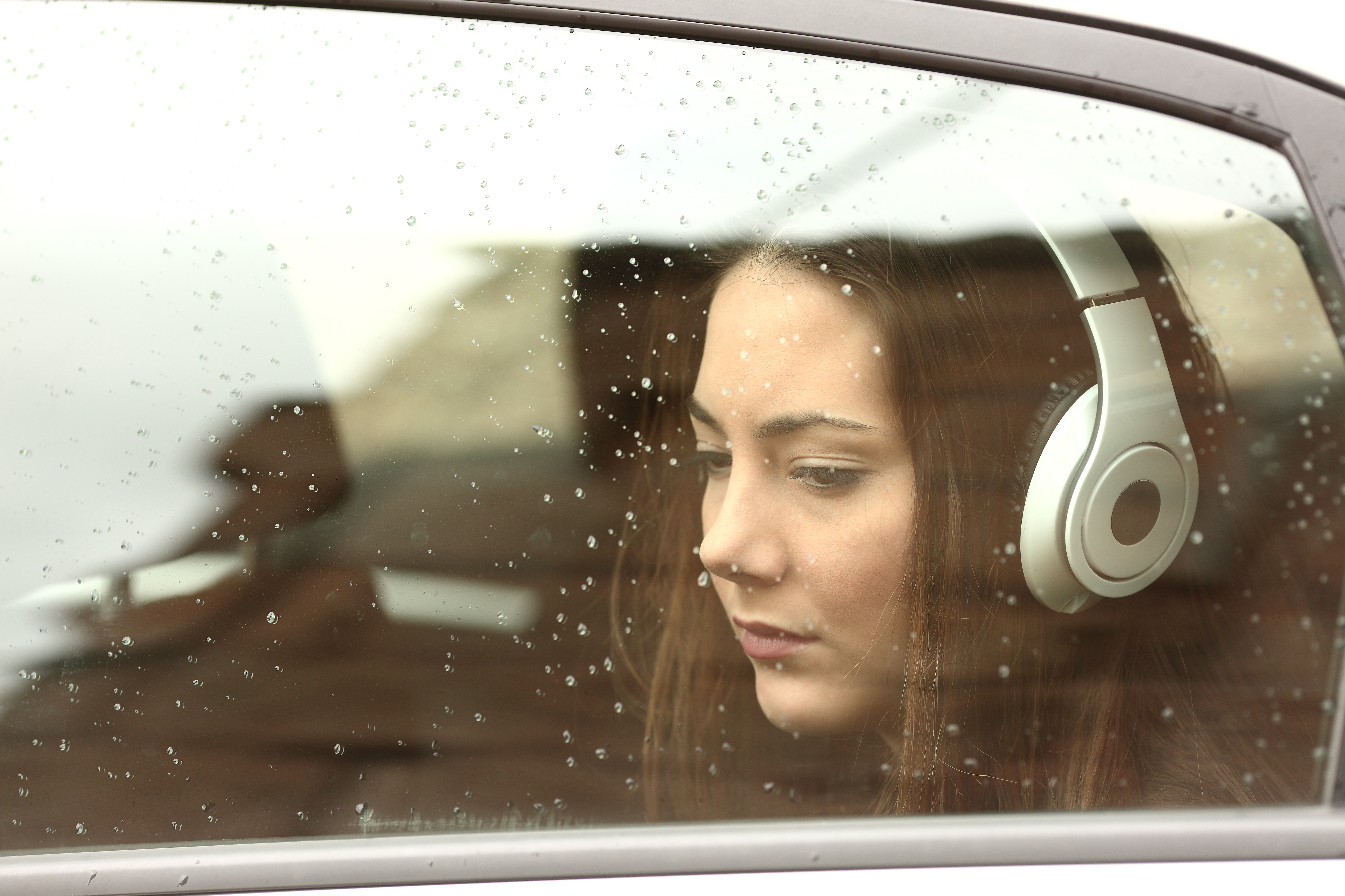 Sad teenager girl inside a car with headphones listening to the music
